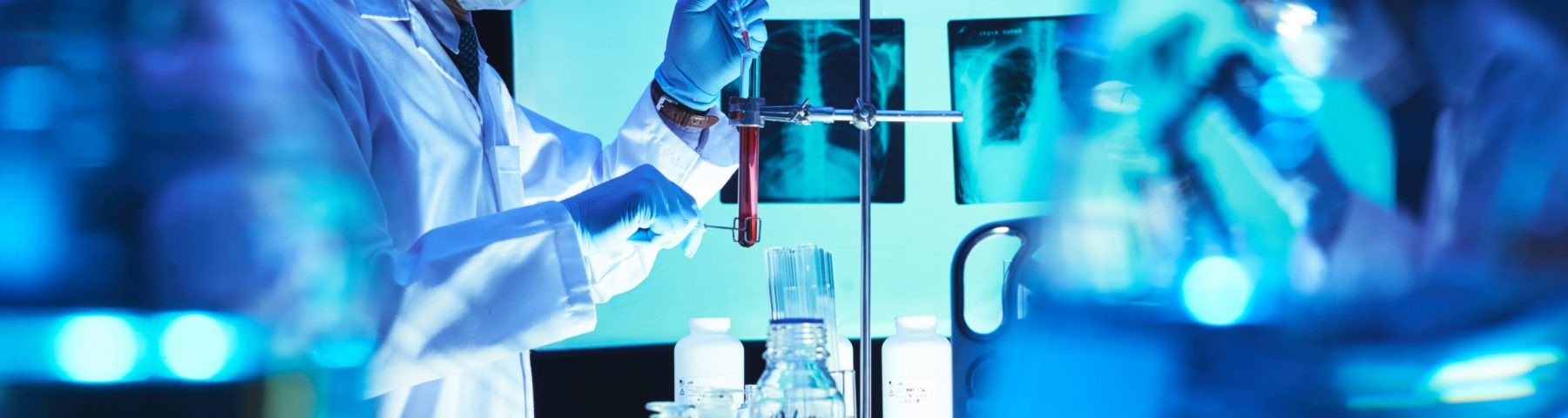 Chemist adding reagent in test-tube